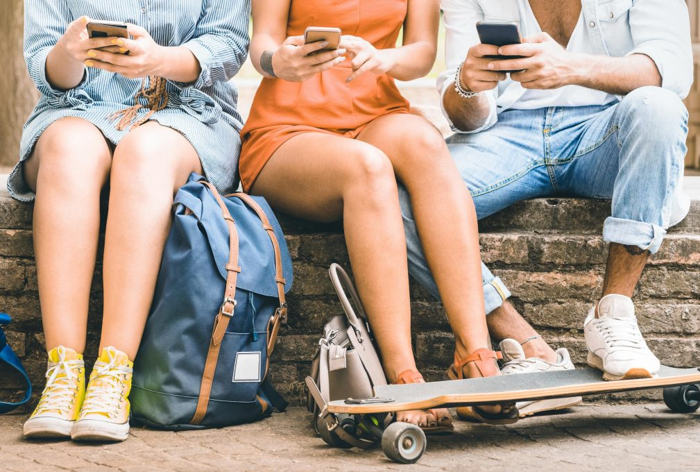 Group of millennial friends having fun spending time together with mobile smartphones and skateboard - Youth friendship concept with young people sharing content on smartphones - Vivid vintage filter