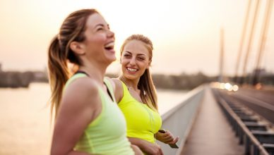 two women leaning against a bridge mid workout