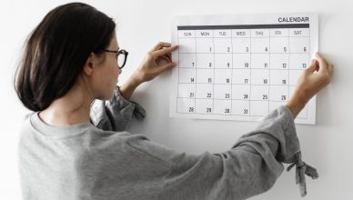 woman posting a calendar on a wall