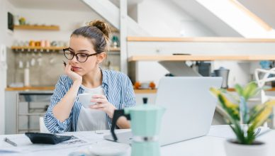 woman sitting in a kitchen looking at her finances