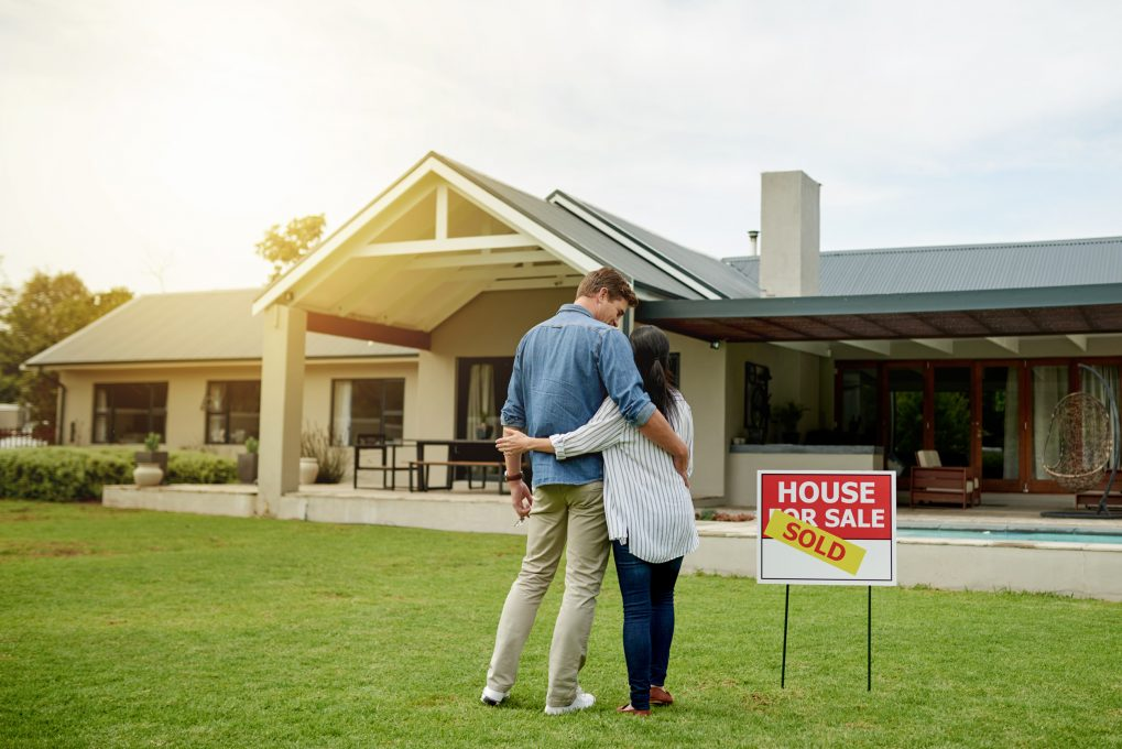 a couple stands on a lawn with a sold sign on a house